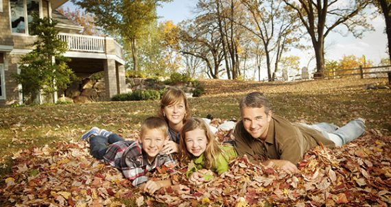 Subject: Casual portrait of family in their backyard of their home in Autumn.