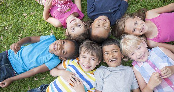 Niños sonriendo en el pasto.