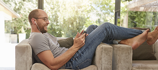 Side view image of a happy mature man using digital tablet while sitting on the sofa at home. Caucasian man relaxing on couch looking at tablet pc and smiling.