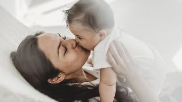 Mother kissing baby daughter hammock in natural light studio