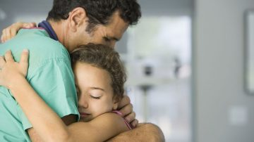 Doctor hugging young patient